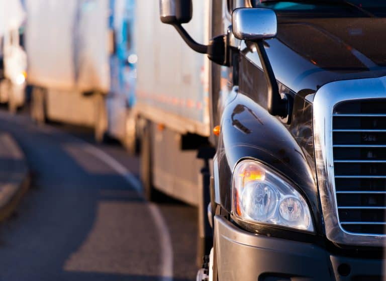 Details of dark semi truck on the road on blured truck and trailer background